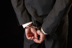 Businessman in suit in handcuffs