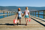 Two children holding hands on ocean pier
