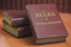 A book with the title Rules and Regulations on the cover