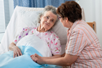 Senior being comforted by nurse in bed